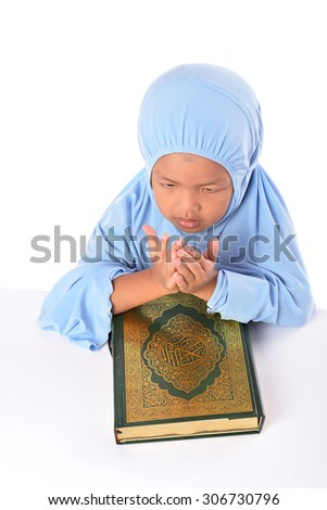 Young Asian Muslim girl make in doa or praying in blue hijab before reading Al Quran - stock photo