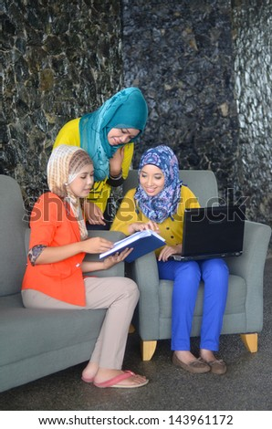 Young asian muslim woman in head scarf in study group - stock photo