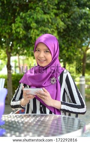 Young asian muslim woman in head scarf smile at cafe - stock photo