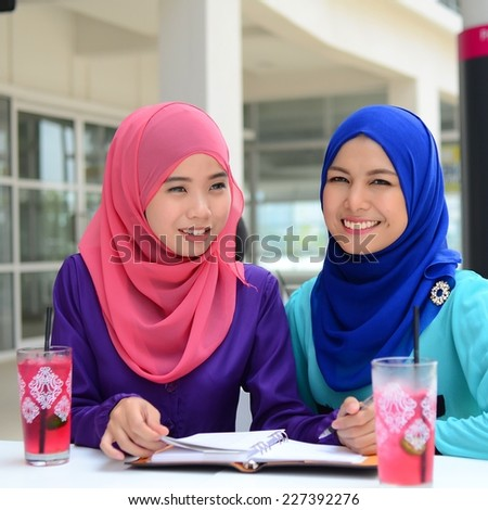 Young asian muslim woman in head scarf smile at cafe study together - stock photo