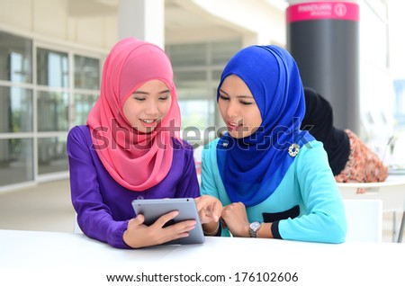 Young asian muslim woman in head scarf smile at cafe surf internet