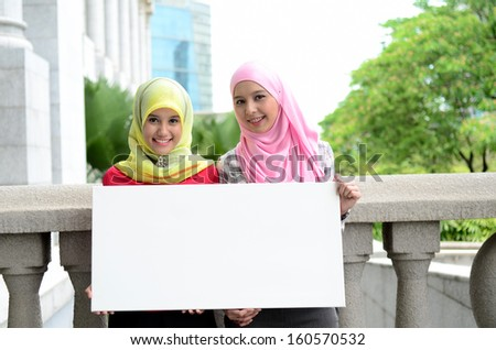 Young asian muslim woman in head scarf smile holding white board - stock photo