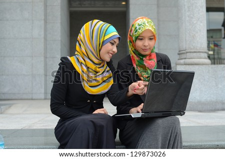 Young asian muslim woman in head scarf smile surf internet - stock photo