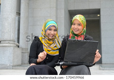 Young asian muslim woman in head scarf smile together - stock photo