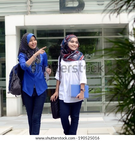 Young asian muslim woman in head scarf smile while walking together - stock photo