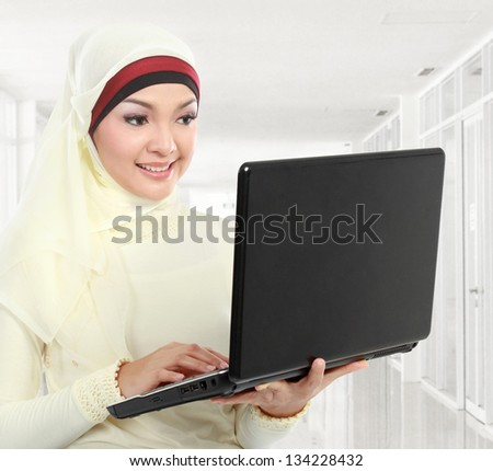 young asian muslim woman in head scarf using laptop computer in the office - stock photo