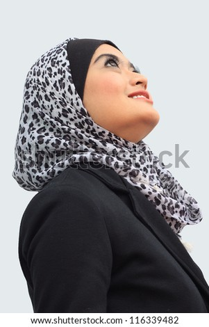 Young asian muslim women smile while looking at above - stock photo