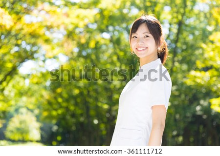 young asian nurse in the park - stock photo