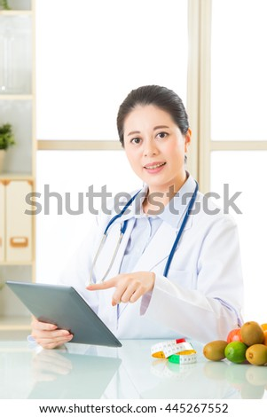 Young asian nutritionist doctor using digital tablet, diet plan - stock photo