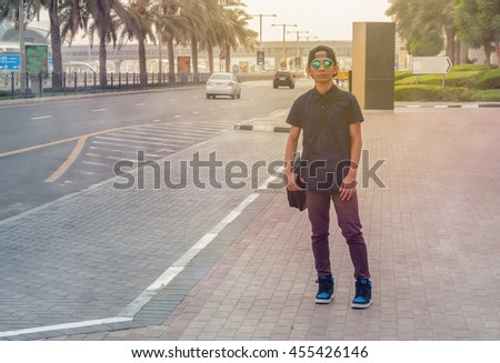 Young asian posing beside the road in Dubai