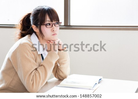 young asian school girl studying in classroom