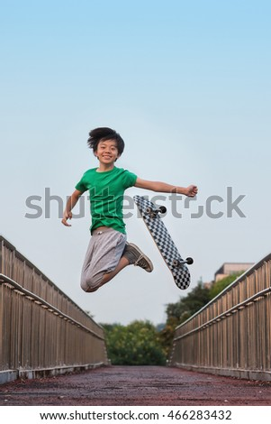 Young Asian skateboarder jumping in the air in joy