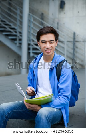 young asian student holding book sitting at campus - stock photo
