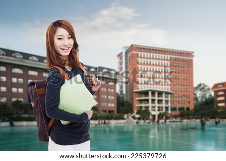 Young Asian student  outdoor shot with campus background.  - stock photo
