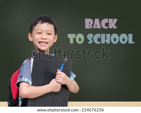 "Young Asian student smiling in front of chalkboard with text ""Back to school"
