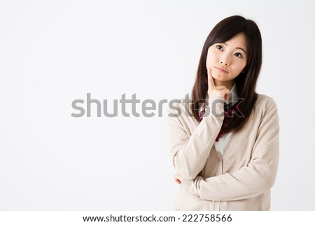 young asian student thinking on white background - stock photo
