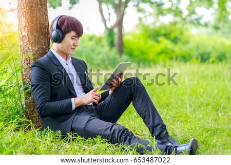 Young asian student working on tablet outdoors in park, education concept, or listening to music