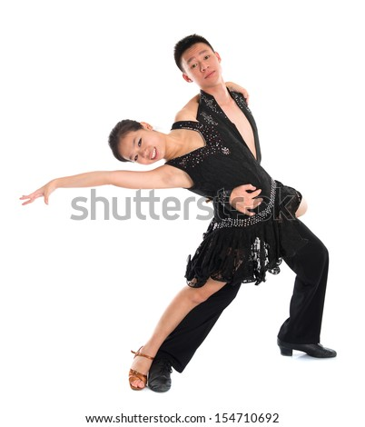 Young Asian teens couple latin dancers dancing in front of the studio background, full length isolated white. - stock photo
