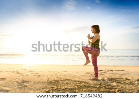 Young Asian Thai woman do Yoga on the sand beach during sunrise to relax and meditation in summer