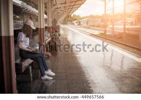 Young Asian tourist with luggage waiting train in station