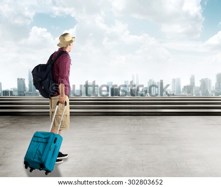 Young asian traveler walking in the city carry a suitcase - stock photo