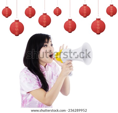 Young asian woman announcing chinese new year with a megaphone - stock photo
