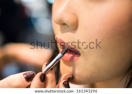 Young Asian woman applying lipstick and other cosmetics