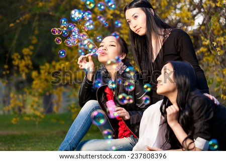 Young Asian Woman Blowing Bubbles in the park - stock photo