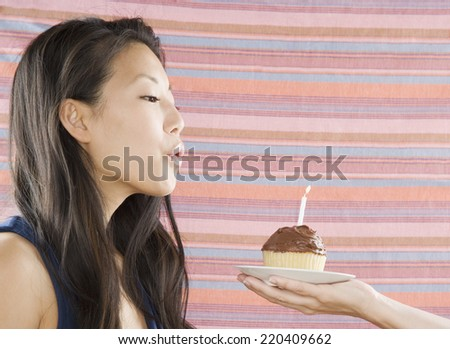 Young Asian woman blowing out candle on cupcake - stock photo