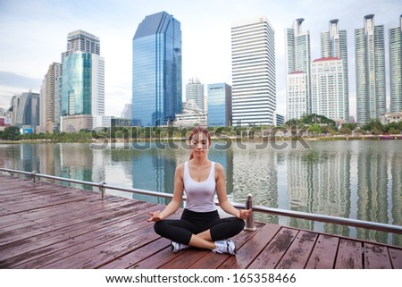 Young asian woman doing yoga exercises at the city park - stock photo