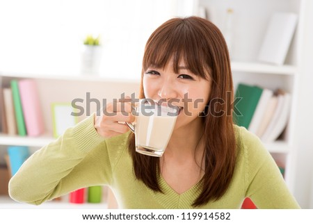 Young Asian woman drinking a glass of soy milk at home - stock photo