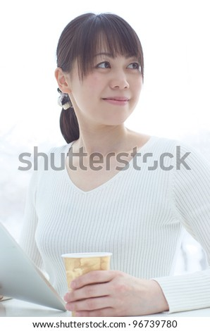 Young Asian woman drinking coffee and using tablet pc