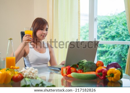 Young asian woman drinking orange juice and using internet at home - stock photo