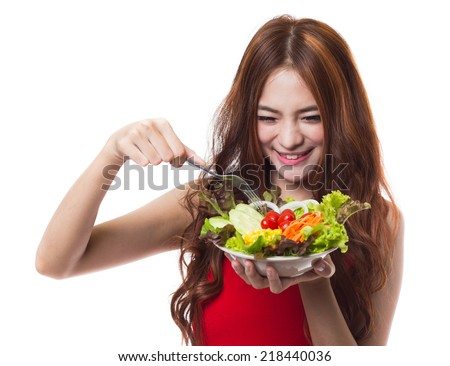 Young asian woman eating fresh vegetable salad on white background