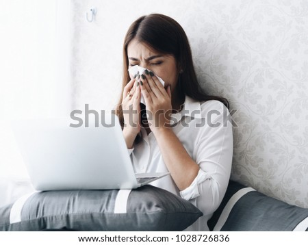 Young Asian woman feeling unwell,she's sneeze always during working with tablet in living room.