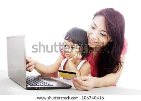 Young asian woman gives online shopping education to her daughter - stock photo