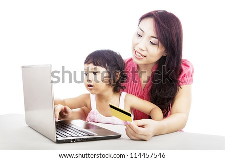 Young asian woman gives online shopping education to her daughter by using laptop and credit card - stock photo