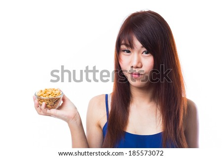 Young asian woman holding a bowl full of peanuts on white background