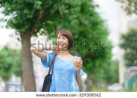 Young Asian woman holding a coffee cup and walking a city street. - stock photo