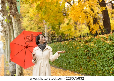 Young Asian woman holing up red umbrella. - stock photo