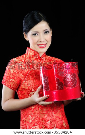 Young asian woman in a chinese dress receiving a gift - stock photo
