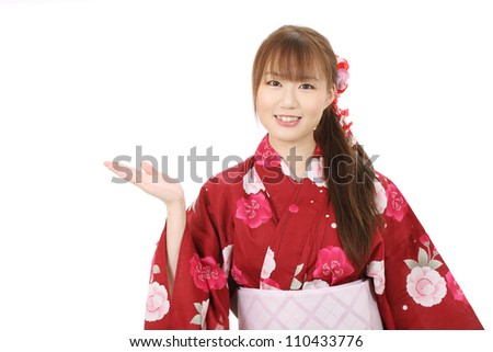 Young asian woman in clothes of kimono hand showing blank sign - stock photo