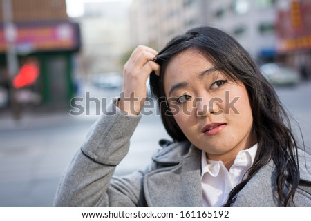 Young Asian woman in coat on a street in a large city