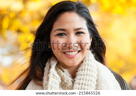 Young Asian woman in mid 20s head and shoulder outdoor autumn headshot portrait - stock photo