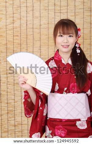 Young asian woman in traditional clothes of kimono with paper fan, on bamboo blind background - stock photo