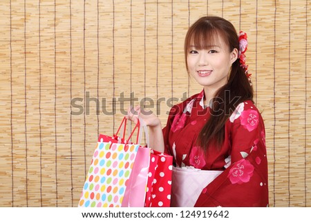 Young asian woman in traditional clothes of kimono with shopping bags - stock photo