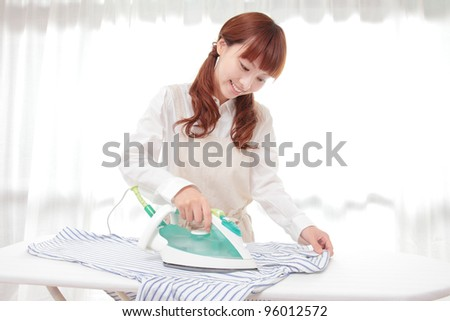 Young Asian woman ironing at the window