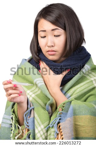 Young asian woman is holding thermometer in hand. She has temperature. - stock photo