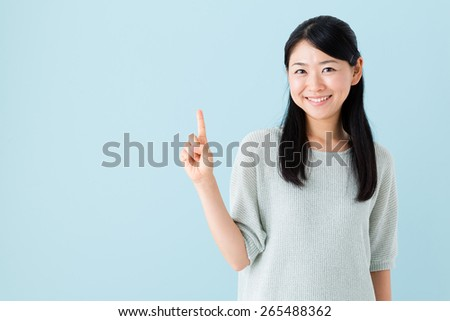 young asian woman isolated on blue background - stock photo