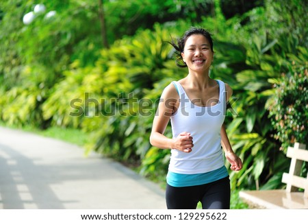 young asian woman jogging  at park - stock photo